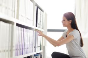 Women looking through binders on a shelf