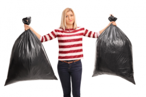 Woman holding up two different trash bags