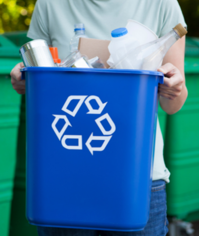 Person carrying a blue recycling bin